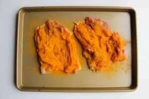 Chicken marinating in curry powder.