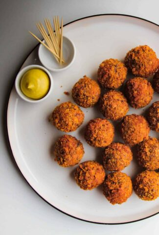 Bitterballen on a plate with mustard and toothpicks on the side.