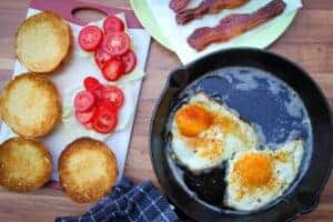 Cooking the eggs in the bacon fat in a cast iron pan.