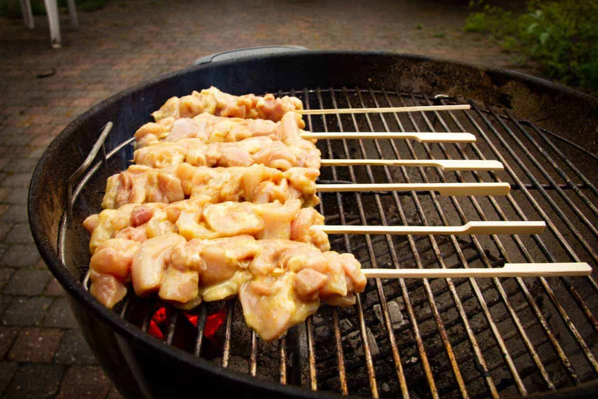 Grilling the chicken skewers on the hottest part of the grill.