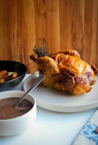 A roast chicken dinner with roast chicken, roasted potatoes and a mushroom gravy on the side.