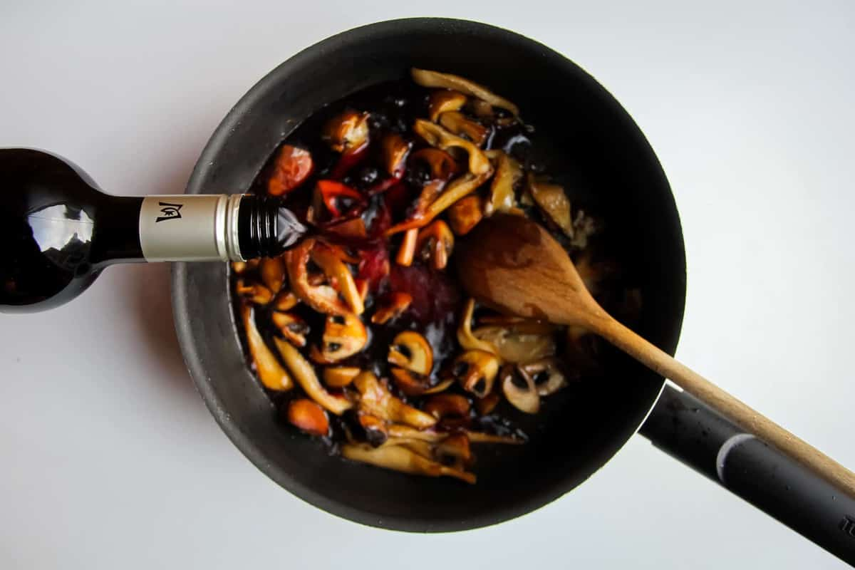 Cooking the mushrooms in a pan and deglazing with red wine.