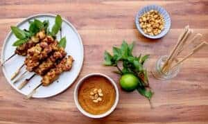 charcoal chicken satay on a plate with basil and peanut sauce.