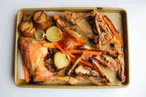 The roasted chicken bones and vegetables on a tray.