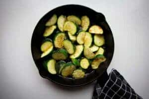 Courgette cooking in a cast iron pan.