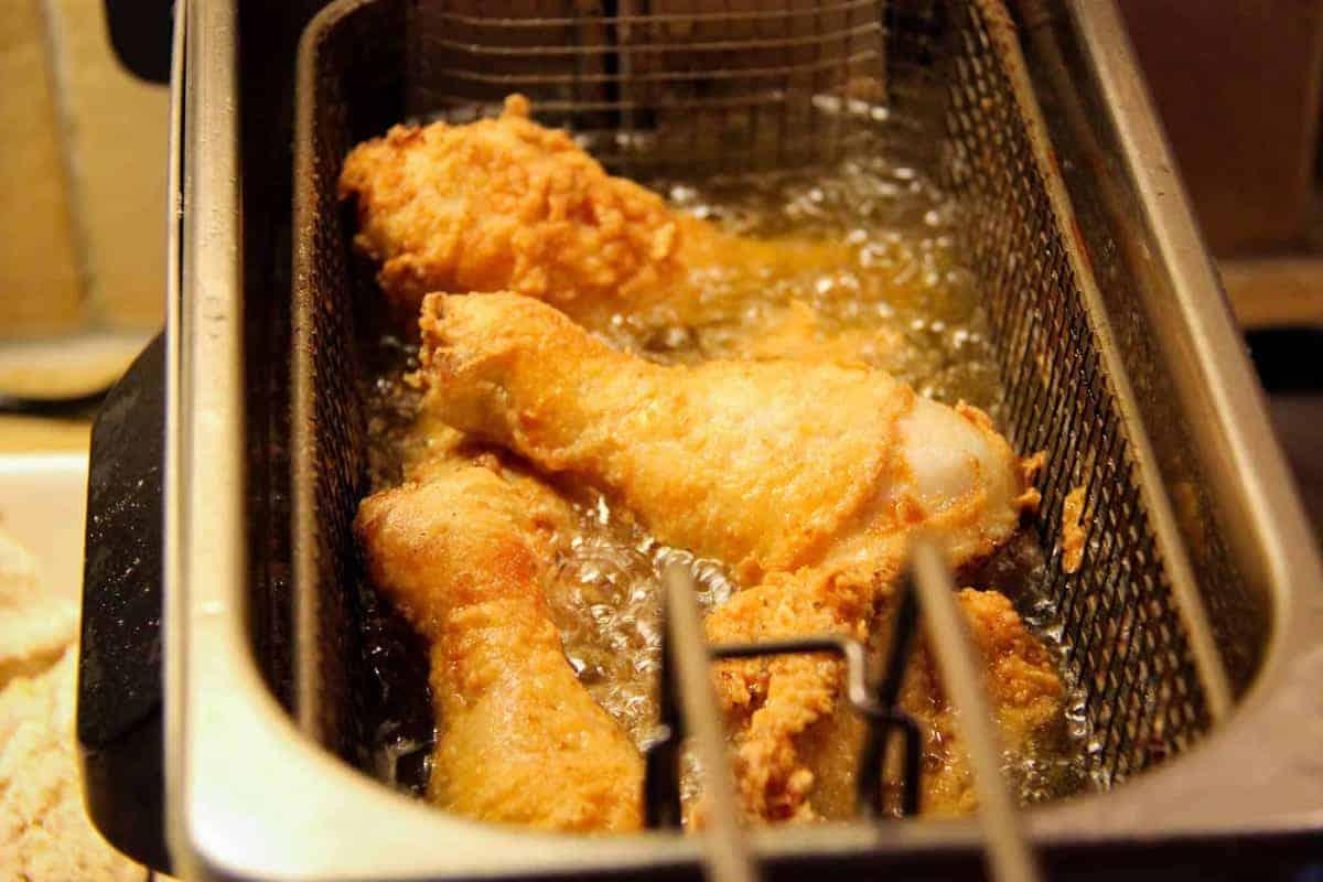 Frying the chicken in a deep fryer.