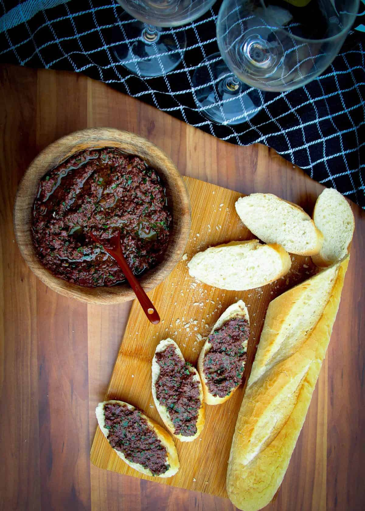 Olive tapenade in a bowl with a french baguette on the side.