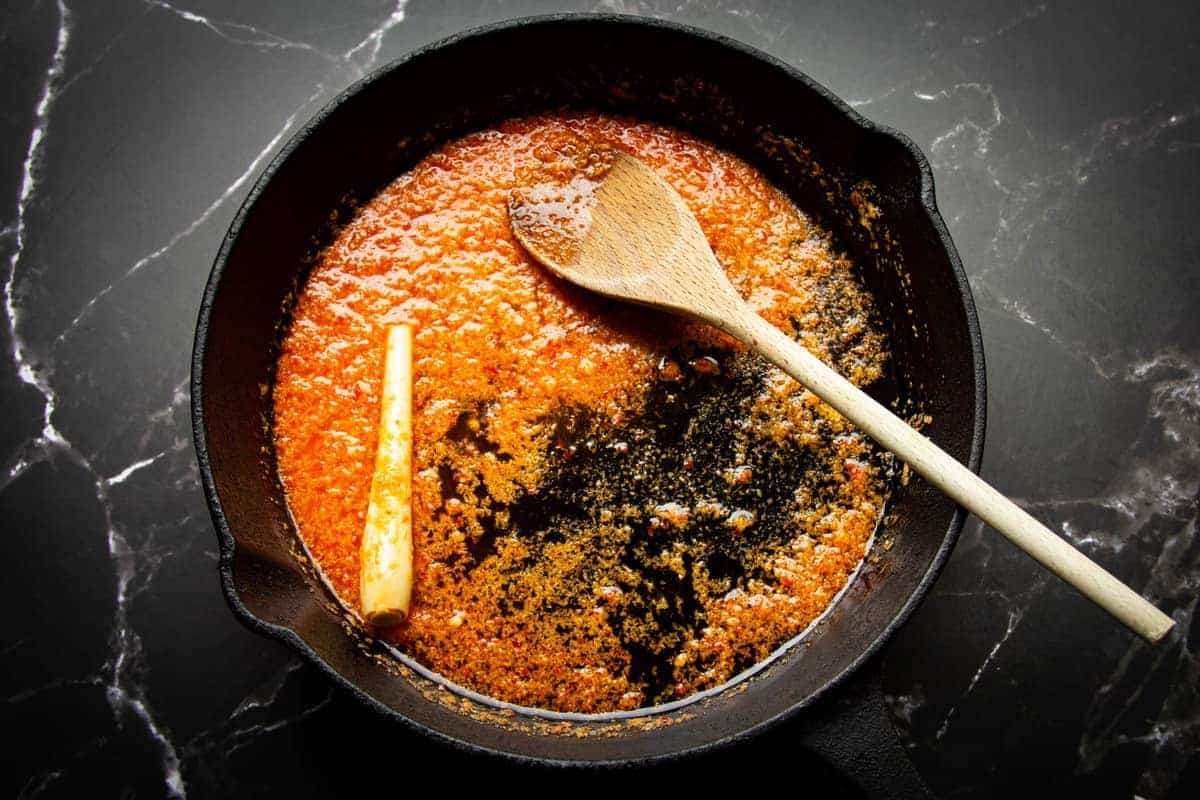 Cooking the spice paste with the lemongrass in a pan.