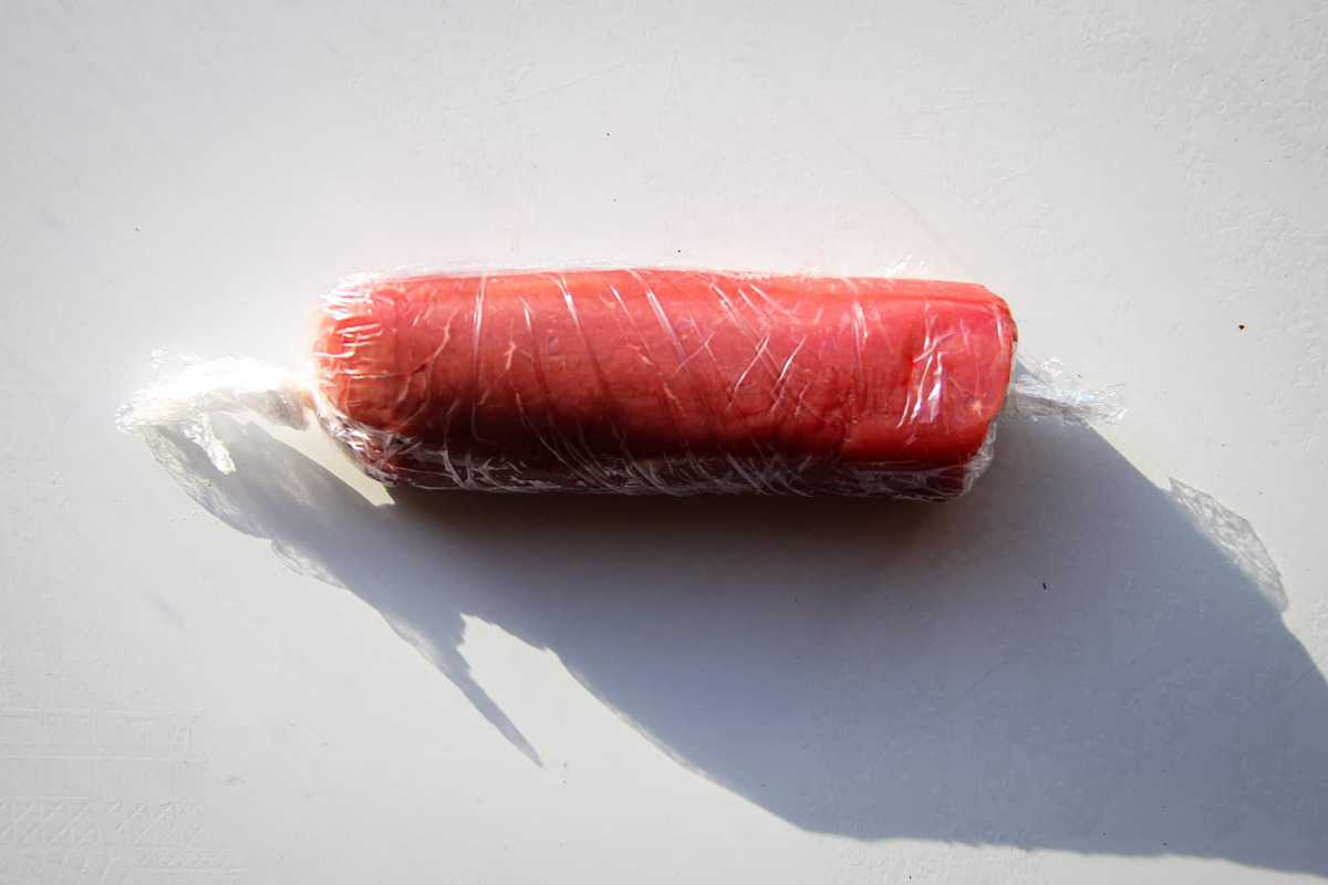 The meat wrapped in plastic wrap to keep a nice shape.