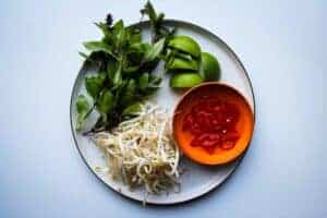 Fresh basil, sliced chili, bean sprouts and fresh lime wedges on a plate.