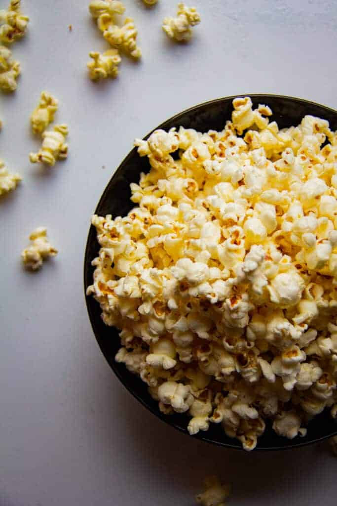 Popcorn in a bowl with some spilling out the sides.