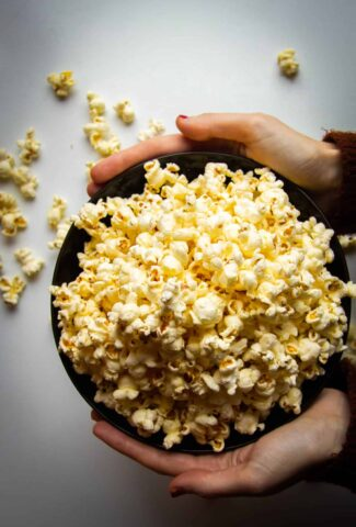 Buttery stovetop popcorn in a bowl being held by two hands.