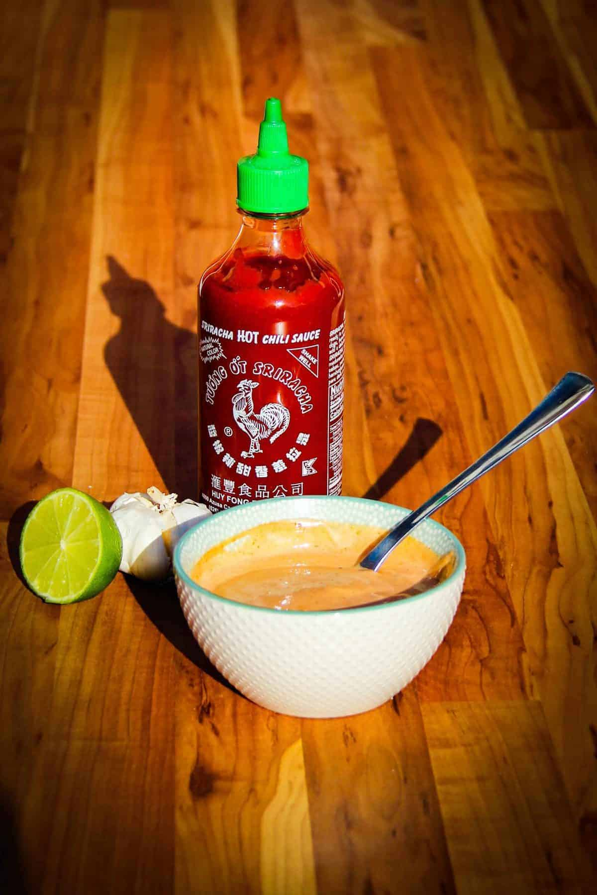 Spicy mayo in a bowl with a sriracha bottle, garlic and lime.