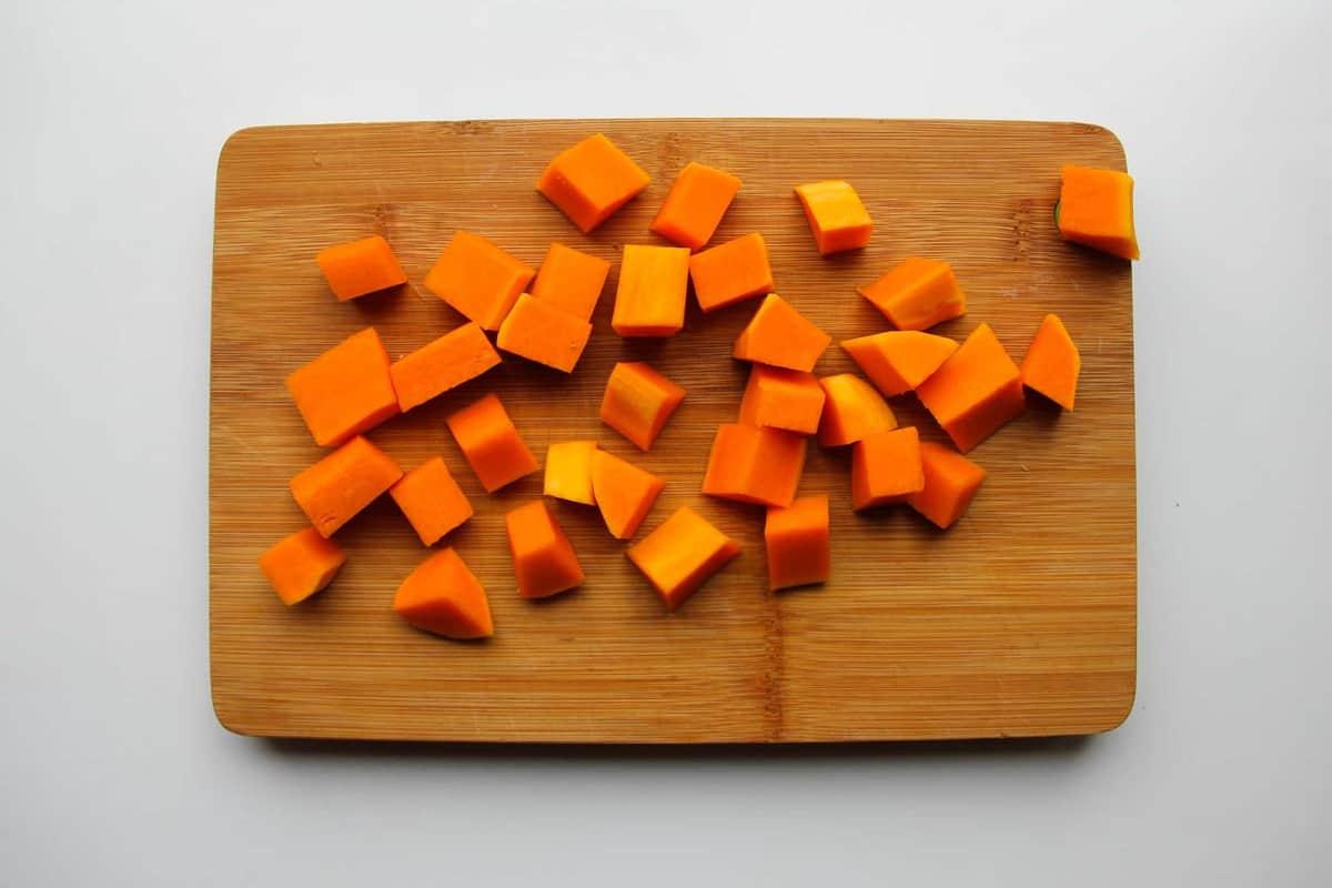 Butternut squash diced up on a cutting board.