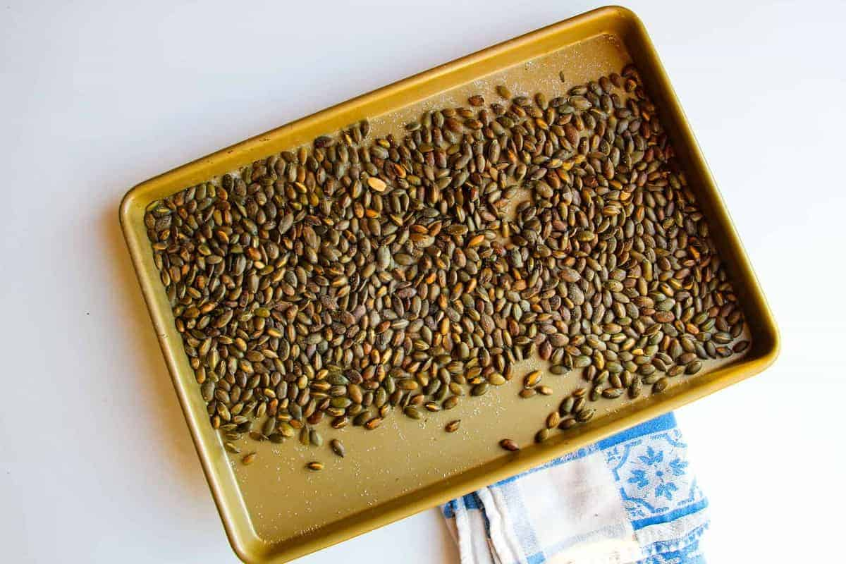 Toasting the pumpkin seeds on a tray.