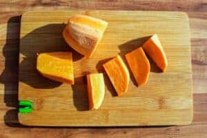 Cutting the raw sweet potato on a wooden board.