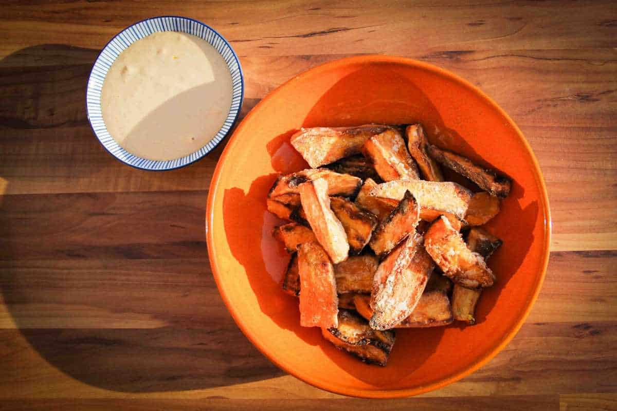 The finishes sweet potato fries in a bowl with spicy mayo on the side.