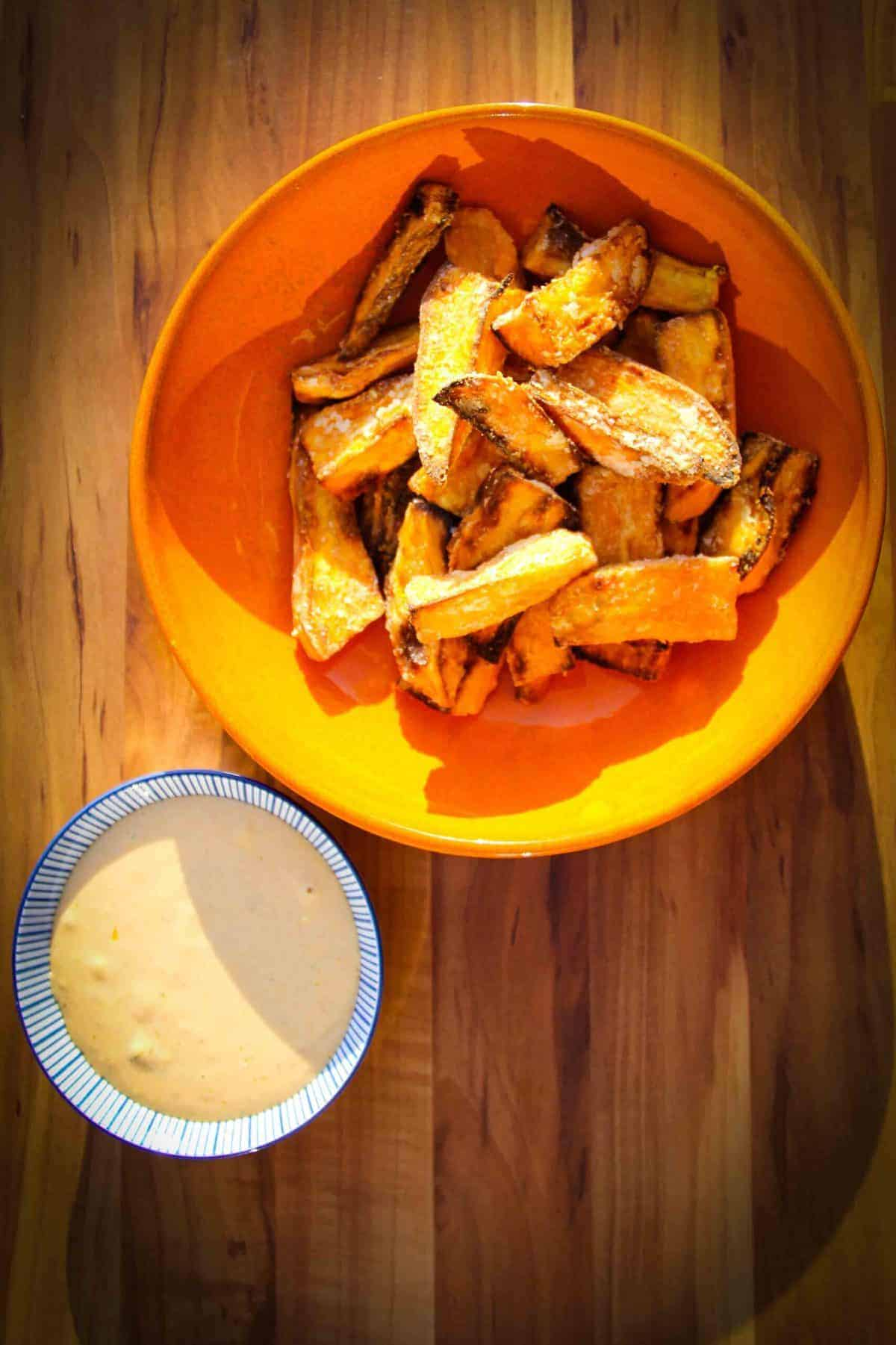 Sweet potato fries in a bowl with spicy mayo on the side.