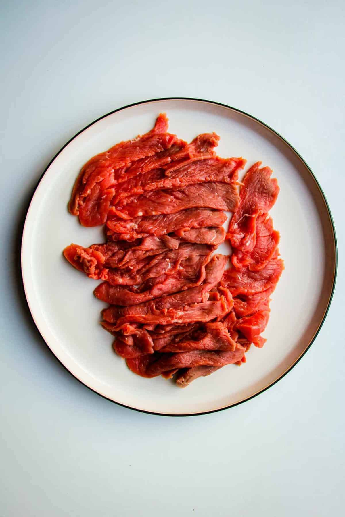 Thinly sliced raw beef on a plate.