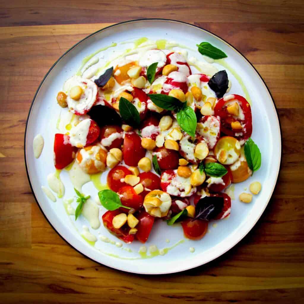 A tomato salad on a plate with basil and a macadamia dressing.