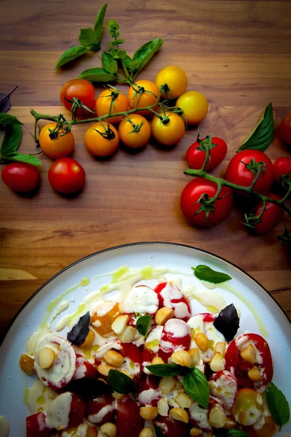 A tomato salad with macadamia dressing on a plate with fresh tomatoes on the side.