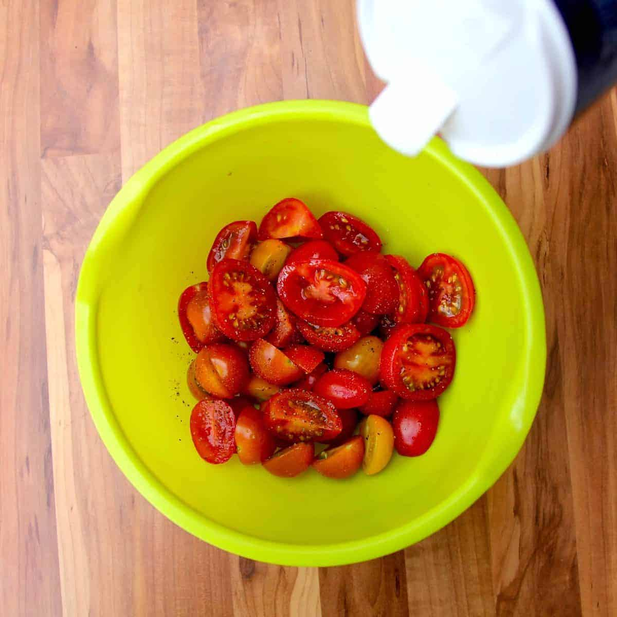 Seasoning the tomatoes in a bowl with sea salt.