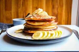 Vegan banana pancakes stacked high on a plate with almonds, fresh banana and maple syrup.