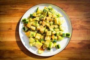 Crunchy apple cucumber salad with miso and sesame on a plate.