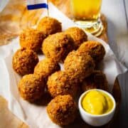 Bitterballen on a board with mustard, a Dutch flag and a cold beer.