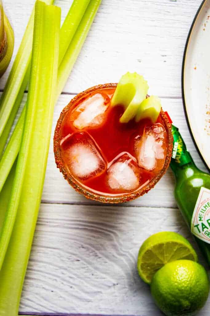 A bbq bloody mary cocktail with celery and lime.