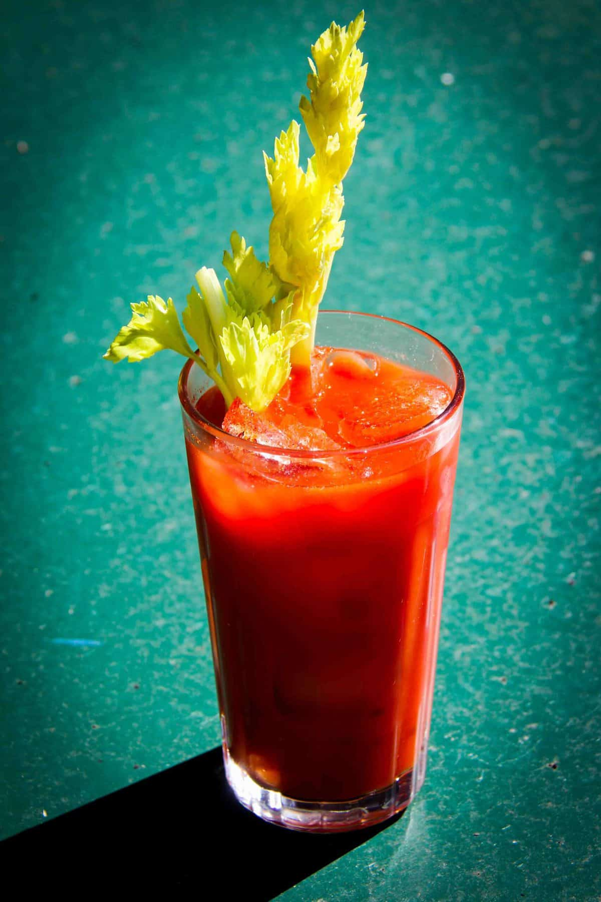 A bloody mary cocktail on a green table.