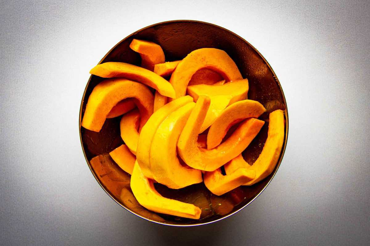 Mixing the squash with the cardamom oil in a bowl.