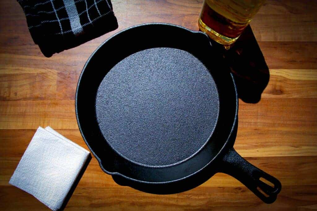 A cast iron pan with oil and a paper towel on the side.