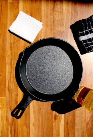 A cast iron pan on a table with oil on the side.