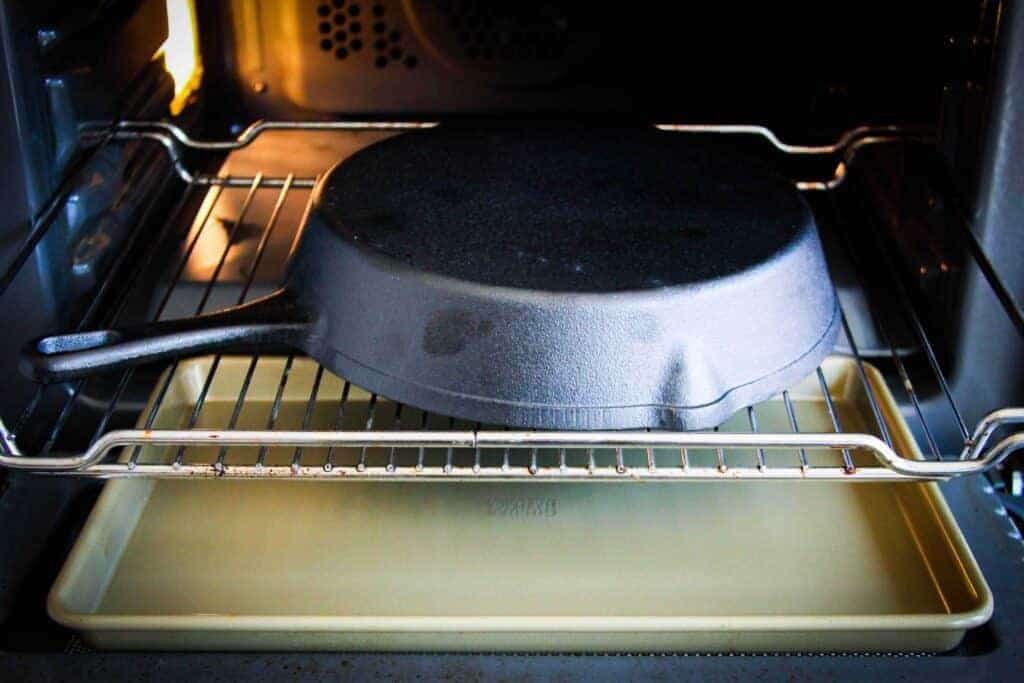 Putting the pan in the oven with a tray underneath.