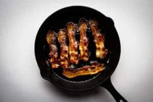 Cooking the bacon in a cast iron pan.