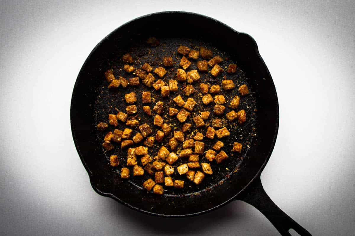 Cooking the croutons for the caesar salad in a cast iron pan.