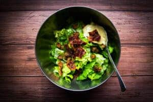 Mixing the caesar salad in a bowl.