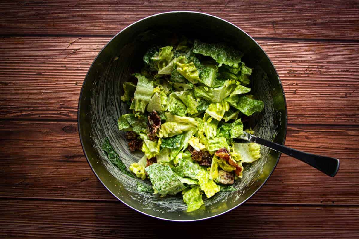 Dressing the caesar salad in a bowl.