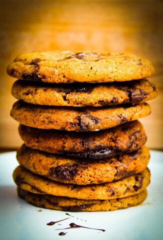 A giant stack of chocolate chip cookies on a plate.
