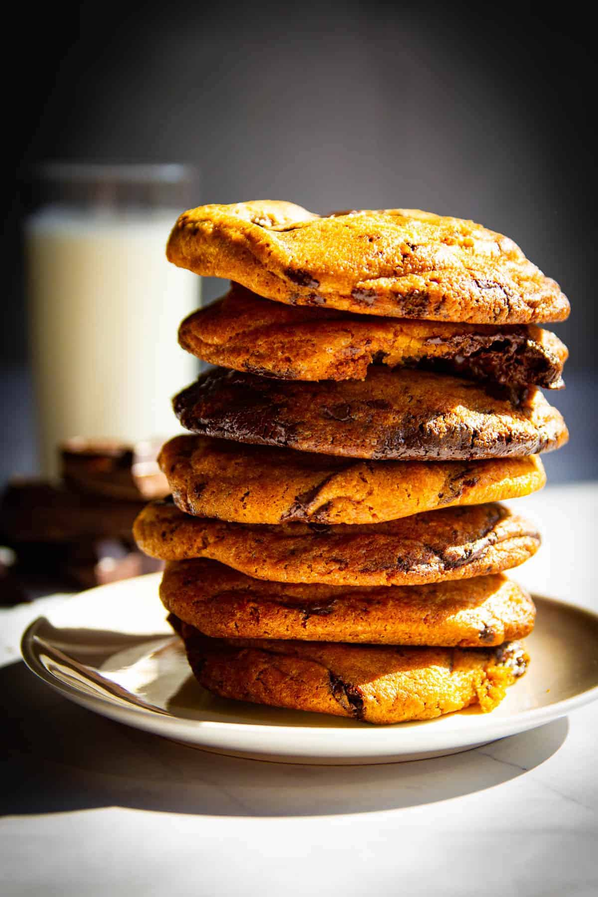A stack of my ultimate chocolate chip cookies with a glass of milk behind it.