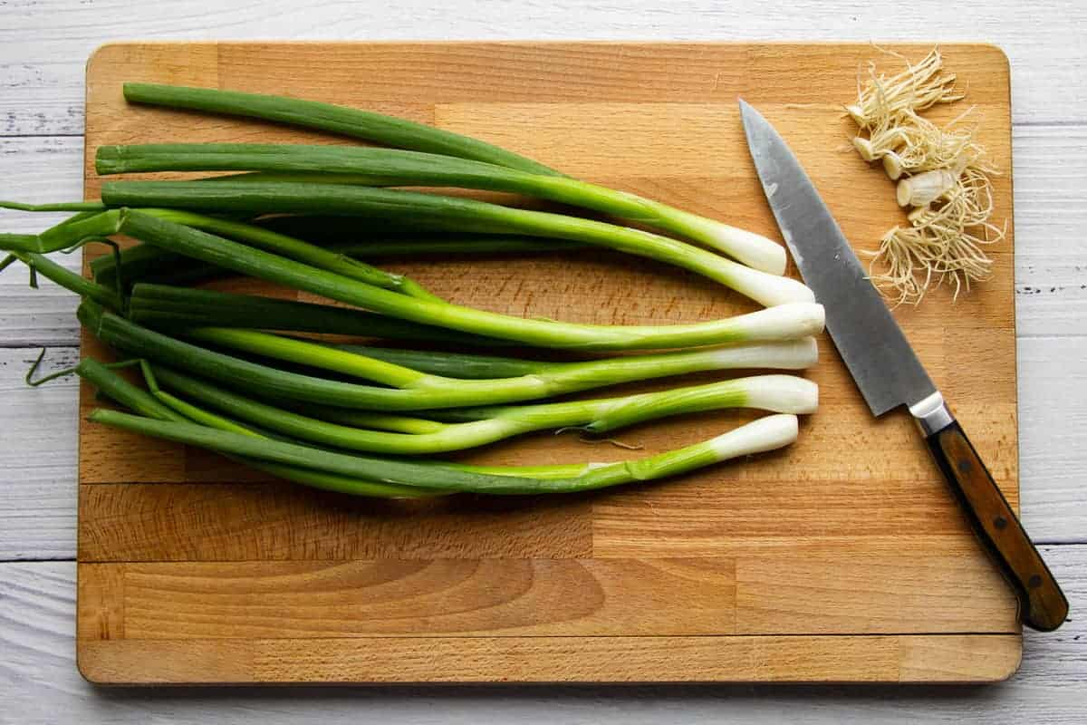 Removing the stems from the green onions.