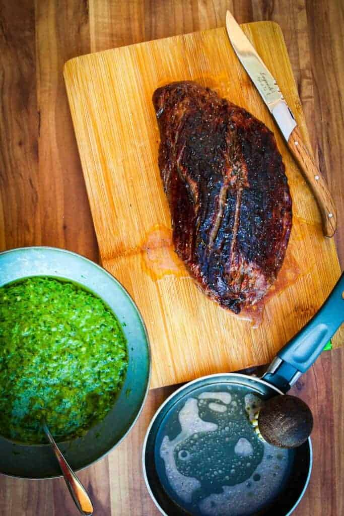 green onion chimichurri with a steak and a pan of butter on the side.