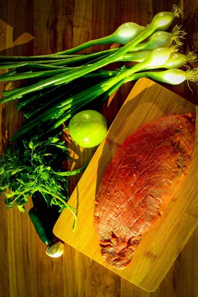 The raw steak, green onions, lime and parsley on a board.