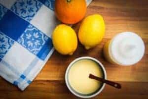 lemon vinaigrette in a bowl with some lemons and oranges.