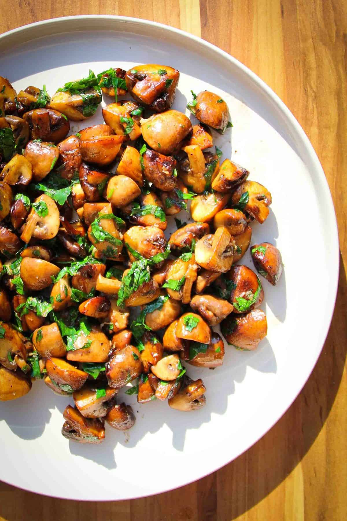 Mushrooms with garlic, butter, parsley and lemon on a plate.