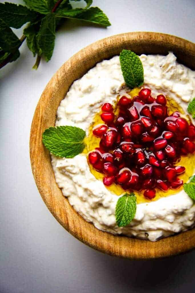 Mutabal, a roasted eggplant dip with garlic, tahini and yoghurt in a bowl with pomegranate and mint.