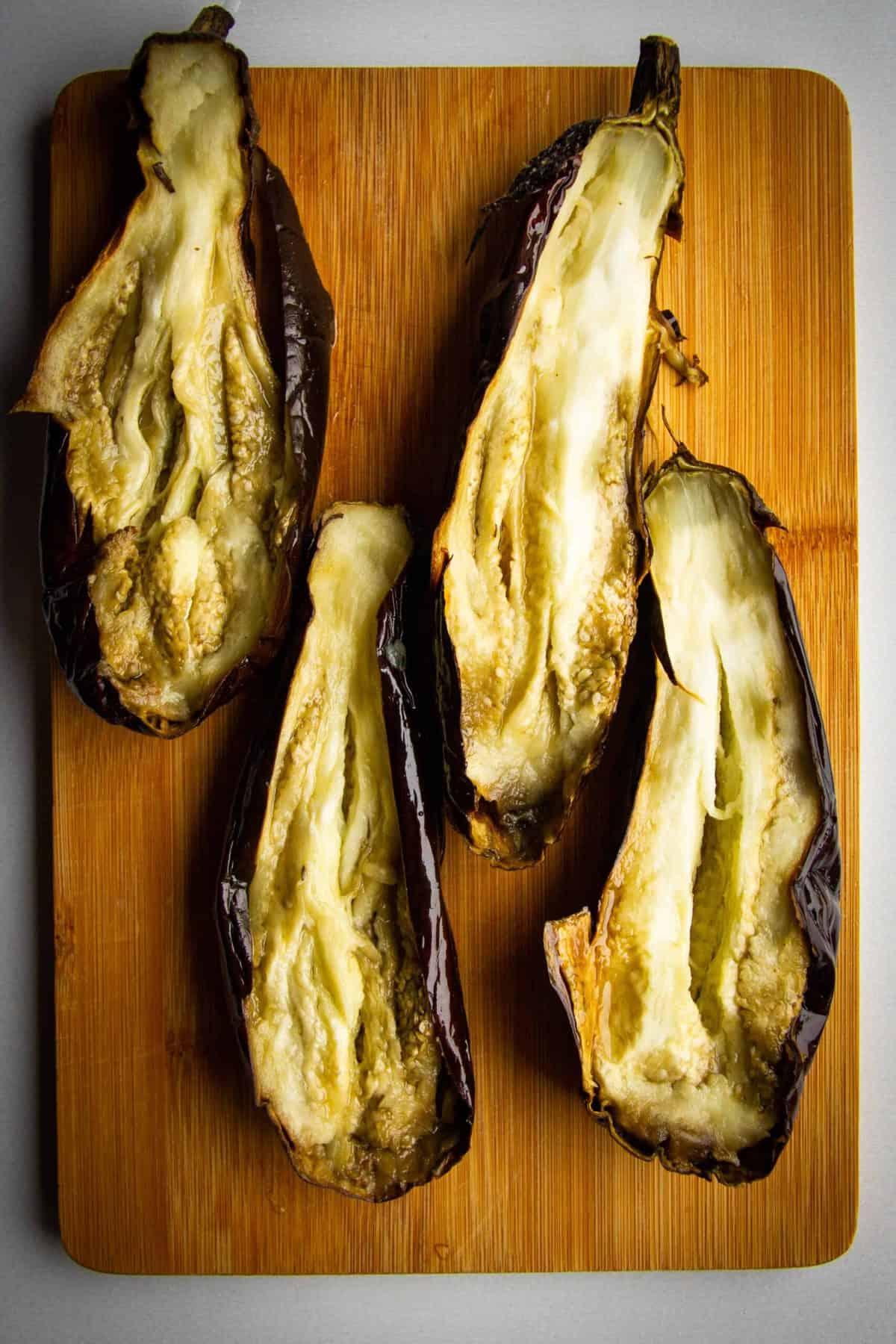 The roasted eggplants split in half on a board.
