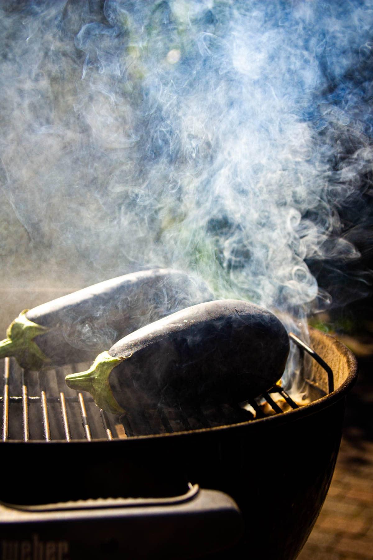 Eggplants smoking on the charcoal grill.