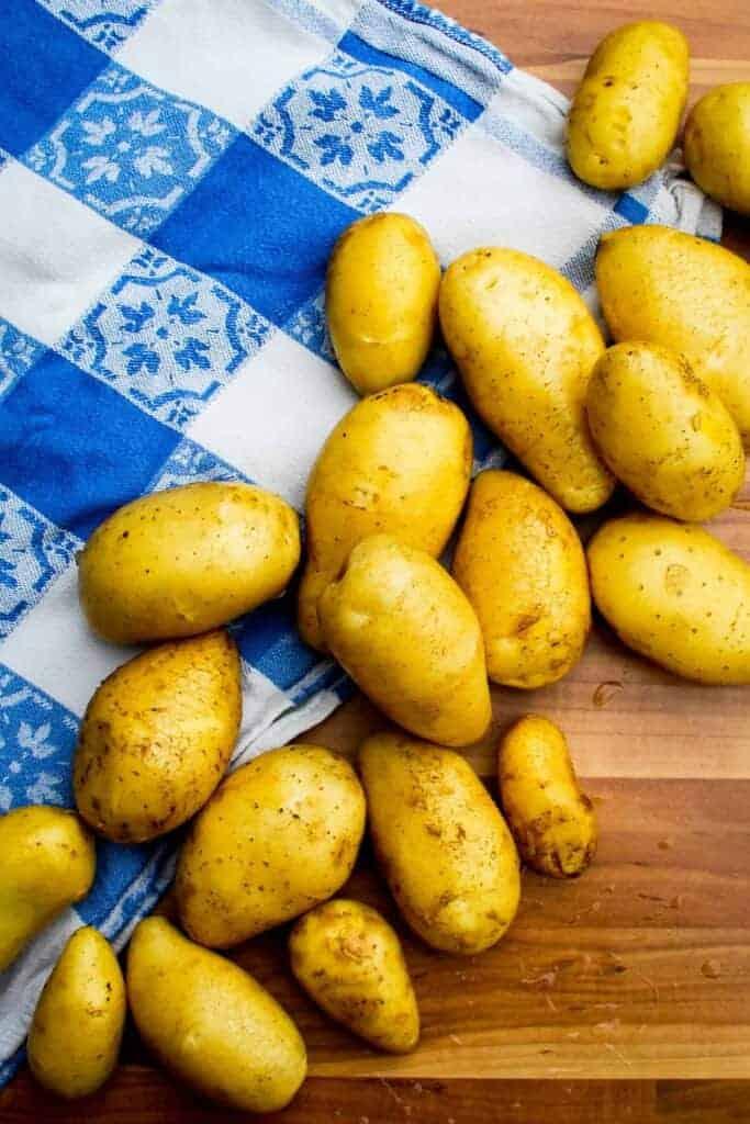 Raw new potatoes on a board.
